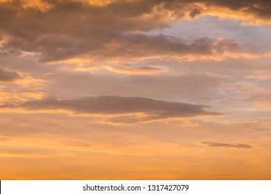 Abstract nature background. Dramatic and moody yellow cloudy sunset sky