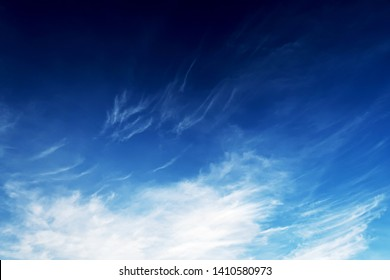 Abstract nature dark background of  white cirrus clouds expanding by wind to cover deep navy blue sky in tropical summer sunlight for backdrop or wallpaper, copy space