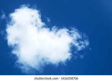 Abstract nature texture background of white puffy & fluffy white clouds with heart shaped formation in beautiful clear blue sky at tropical summer morning sunlight, Valentine's day concept, copy space