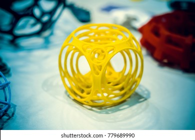 Abstract object of a yellow color printed on a 3d printer on a white table. Fused deposition modeling, FDM. Progressive modern additive technology. Concept of 4.0 industrial revolution