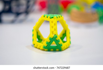 Abstract object of a yellow green color printed on a 3d printer on a white table. Fused deposition modeling, FDM. Progressive modern additive technology. Concept of 4.0 industrial revolution