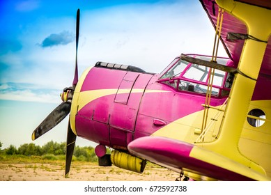 Abstract, old yellow, pink, purple plane in abandoned airport next to dark forest in an overcast day. Military plane, russian aircraft. Soviet mass-produced single-engine biplane at field aerodrome