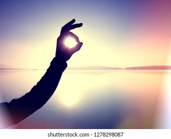 Abstract, over filtered. Hands create funny frame with sunset immersing at the horizon. Autumn evening at the lake.