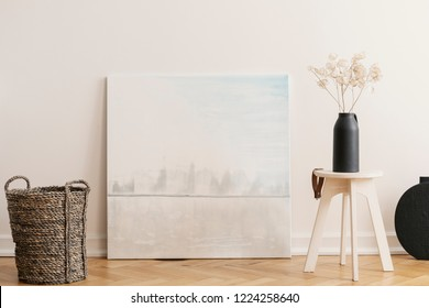 Abstract painting between wicker basket and wooden table with black vase with flowers, real photo with mockup