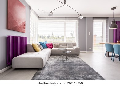 Abstract painting hanging above a purple radiator, and a large sofa with many, colorful pillows in a stylish living room