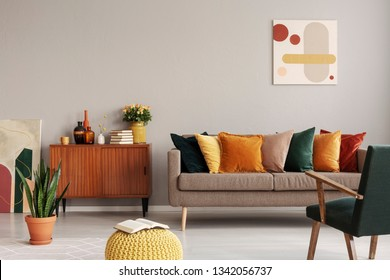 Abstract painting on grey wall of retro living room interior with beige sofa with pillows, vintage dark green armchair and yellow pouf with book