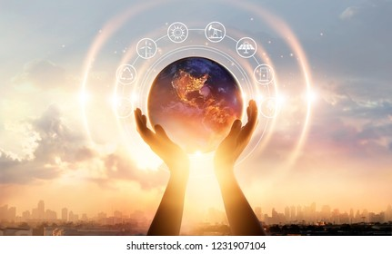 Abstract palm hands touching earth at night on sunset city background. Earth day. Energy saving concept, Elements of this image furnished by NASA