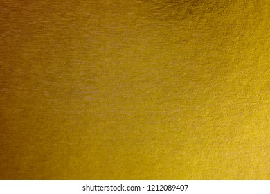 Abstract paper golden foil background for Merry christmas and Happy new year. Gradation gold foil leaf shiny with sparkle yellow metallic texture. top view.