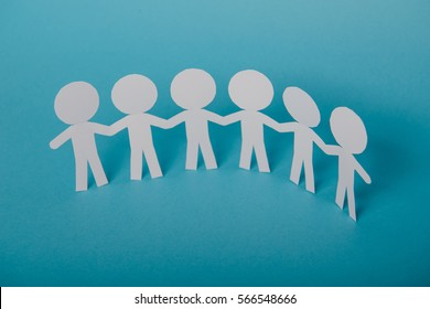 abstract paper people holding for hands on blue background