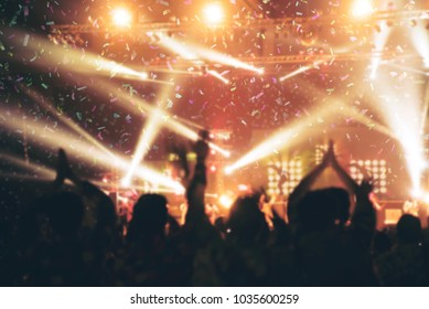 Abstract Party Background - Crowd People Enjoy Dancing and Show Hands Up in the Concert with Beautiful Lighting and Laser