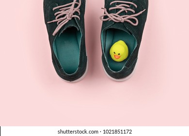 Abstract pastel color Men's shoes with yellow rubber duck on pink. Pranks and tricks concept for April fool's day