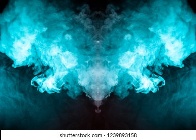 Abstract pattern of colored smoke backlit blue, green and turquoise in the shape of a mystical-looking bird or a ghost-head on a black isolated background. Soul and inner state of thoughts.