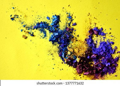Abstract pattern of crushed shinny pigments eyeshadow powder in yellow, blue, violet and purple colors. Top view on yellow background. Modern trendy summer makeup colors.