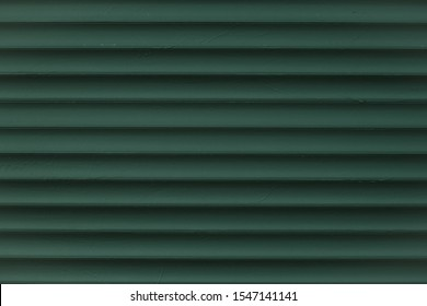 Abstract pattern of lines on dark green background. Vintage texture of grunge metal jalousie. Corrugated metallic surface. Ribbed background with stripes, straight lines. The blind close-up.