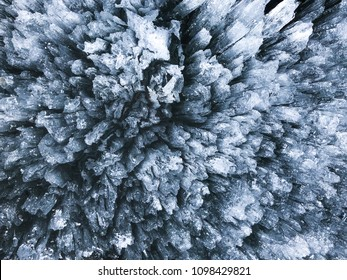 Abstract pattern of melting cristal clear ice on lake (blue, white and black colors), macroshot