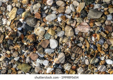 Abstract pebble background. Pebble texture in sea water. Stone background. Sea pebble beach. Beautiful nature. copy space