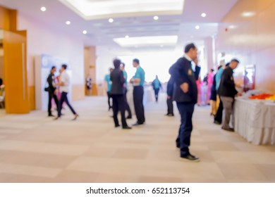 Abstract people walking in exhibition blurred background.