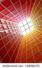 Abstract perspective of vertical lobby ceiling with skylight and strong geometry and symmetry and dramatic colors as background