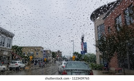 Abstract perspective view of water droplets on a windshield during a rain storm. Blurry background of cloudy skies, buildings & vehicles. Captured on an overcast rainy morning in a city.