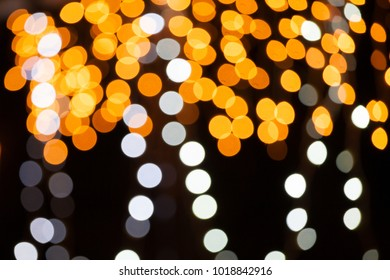 Abstract photo of a dark background with blurred, bright fairy lights