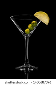 Abstract photo of empty martini glass with olives. On a black background.