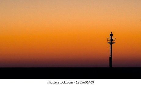 Abstract photo of a light signal or light buoy against a brightly colored sky with beautiful intense colors of the sunset. Minimalsitic image with contrasts and the contours in the port of harlingen