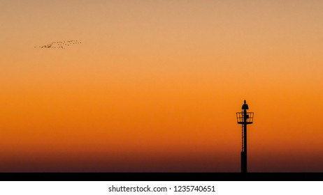 Abstract photo of a light signal or light buoy against a brightly colored sky with beautiful intense colors of the sunset. Minimalitic image with contrasts Background scene with natural autumn light.