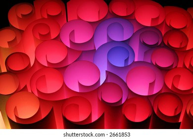An abstract picture of pieces of paper curled into a spiral in different colours in blue pink reds