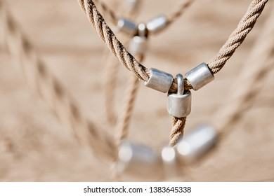 Abstract picture shot on a playground at a climbing frame with a detail with bright beige ropes connected via metal. Seen in Nuremberg, Germany, April 2019