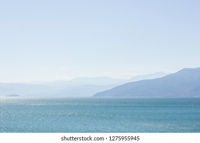 abstract picturesque scenic landscape of big lake natural reservoir foreground and mountain silhouettes in fog with sky background in sun rise morning time