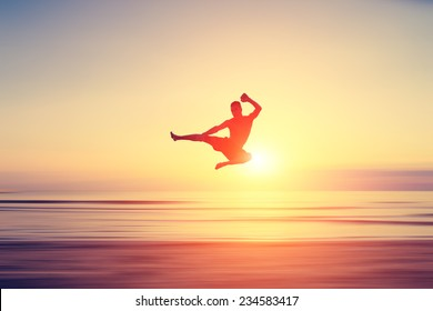 abstract piece of art. man performing flying kick on a blurred surface that looks like a beach at sunset