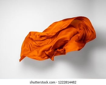 abstract piece of orange fabric flying, high-speed studio shot