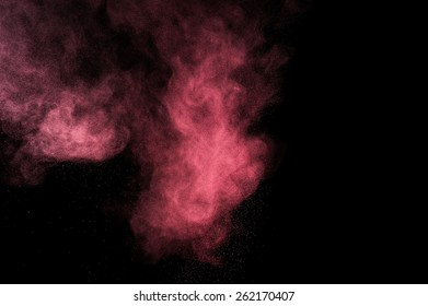 Abstract pink powder explosion on black background.