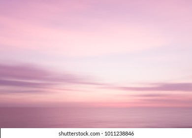 Abstract pink sunset sky and ocean nature background with blurred panning motion.
