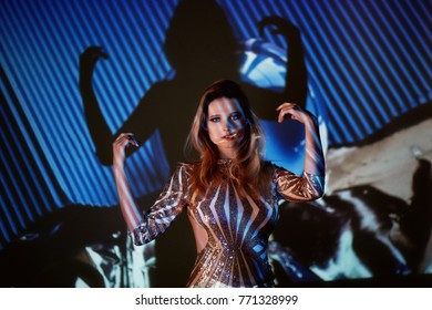 Abstract portrait of a beautiful girl in the light of the projector. The atmosphere of disco 80-x. Golden sequins. A sense of fragility and beauty. Plastic body. Beautiful and mysterious.