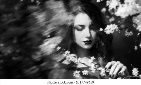 Abstract portrait, girl face with dark lips and downcast eyes, woman in blooming garden, sad and calm, black and white photo, art photography, concept of fantasy and mystical