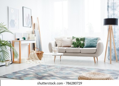 Abstract posters hanging on a bright white wall facing a comfy sofa in a bohemian style day room interior