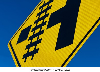 Abstract Railroad crossing sign at angle with blue sky
