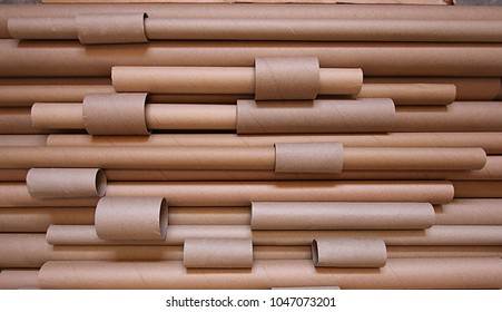 An abstract, random pile of various sized carboard tubes.