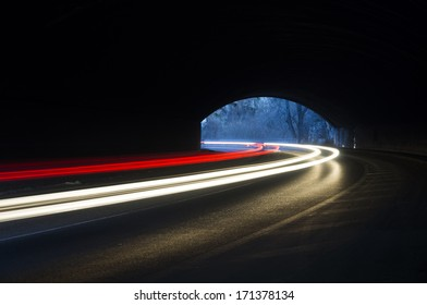 Abstract rays of white and yellow light with a car tunnel as background