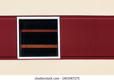 Abstract red and white building wall with a window and shelves