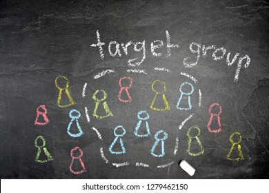 Abstract representation of the target group determination with chalk on a dark stone surface painted figures in different colors