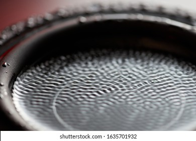 Abstract rippled background texture. Surface of water frozen in time, hi contrast lighting exposes the fascinating patterns created by soundwaves traveling directly through it.