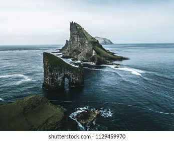 Abstract rock formations and an island covered with green grass and moss in rough sea from bird perspective on a moody day with rain and the sky as a blue background on the Faroe Islands in Europe