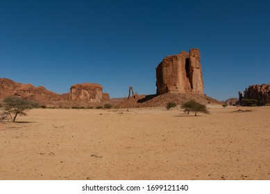 Abstract rocks formation at plateau Ennedi, one in lyre shape in the background, in Sahara desert, Chad, Africa