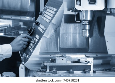 The abstract scene of  CNC milling machine and hand of CNC operator  press the control panel .Hi-precision CNC machining operation concept.