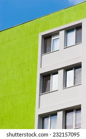Abstract scene of a green apartment building in angle against blue sky and white clouds.