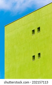 Abstract scene of a green wall in angle with little windows against blue sky and white clouds.