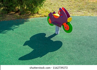 Abstract scene with multicolor wooden toy motorcycle in playground with long shadow on green artificial grass