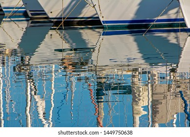 Abstract scene with reflection of moored in harbour luxury sale yachts in sea blue water with ripple and waves. Sailing sport background image